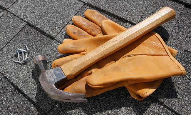 martelo e luvas sobre telhado