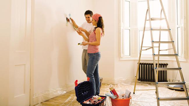 casal preparando parede para revestimento