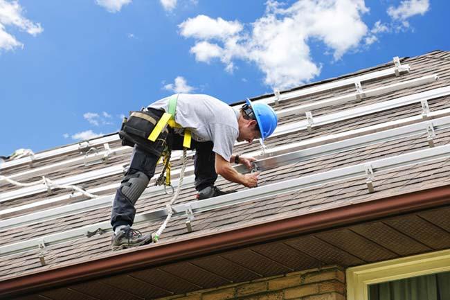 homem com EPI consertando telhado