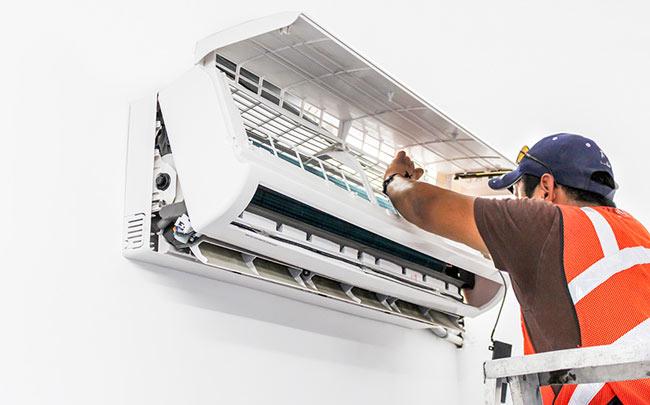 homem fazendo manutenção do ar-condicionado
