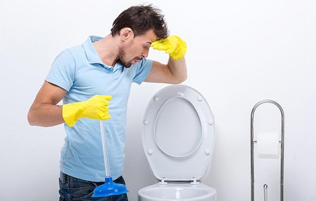 homem desentupindo vaso sanitário